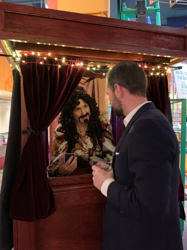 Zoltar entertainer in booth speaks with man