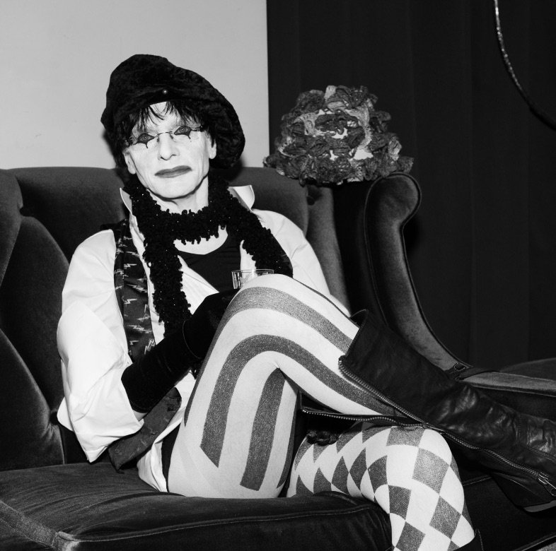 Harlequin sitting on a sofa grinning