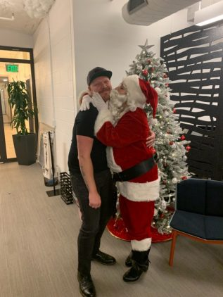 Strolling Entertainers -Santa giving a smiling, grown man a smooch!